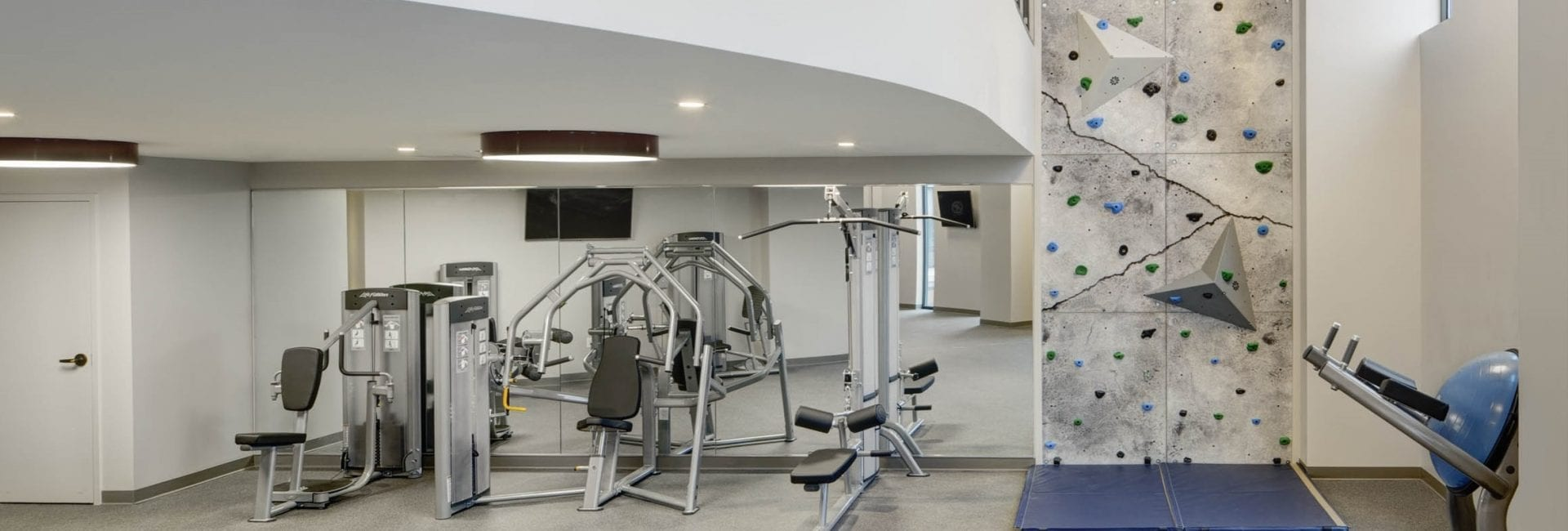 The Kendrick's fitness center including fitness machines and rock climbing wall.