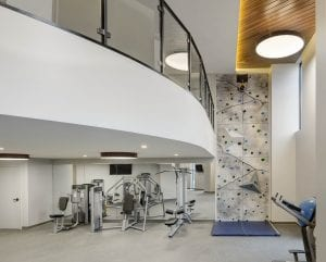 Two-story fitness center with rock climbing wall, fitness machines and natural light.