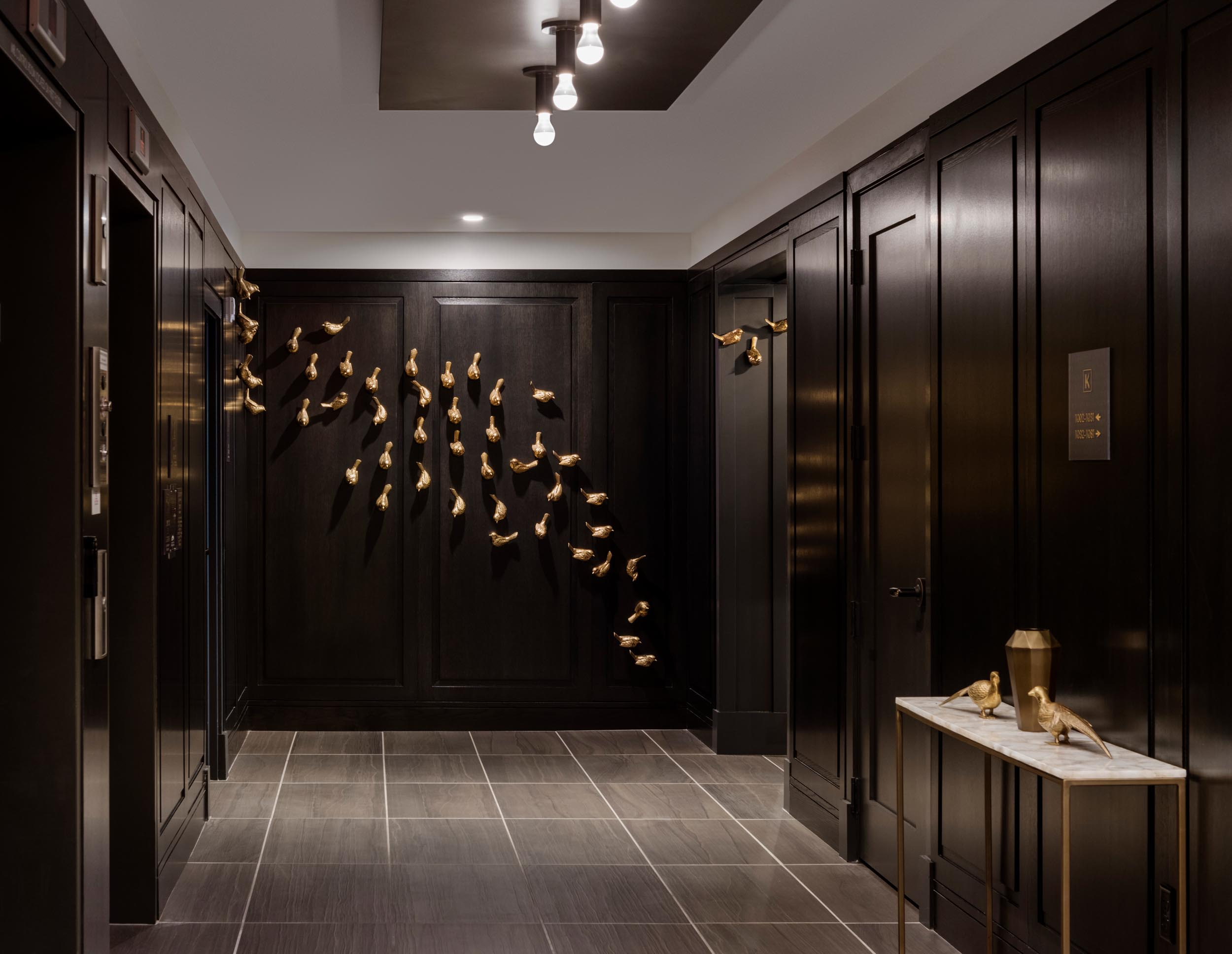 Elevator lobby at The Kendrick with dark wood panel walls and gold metal bird artwork