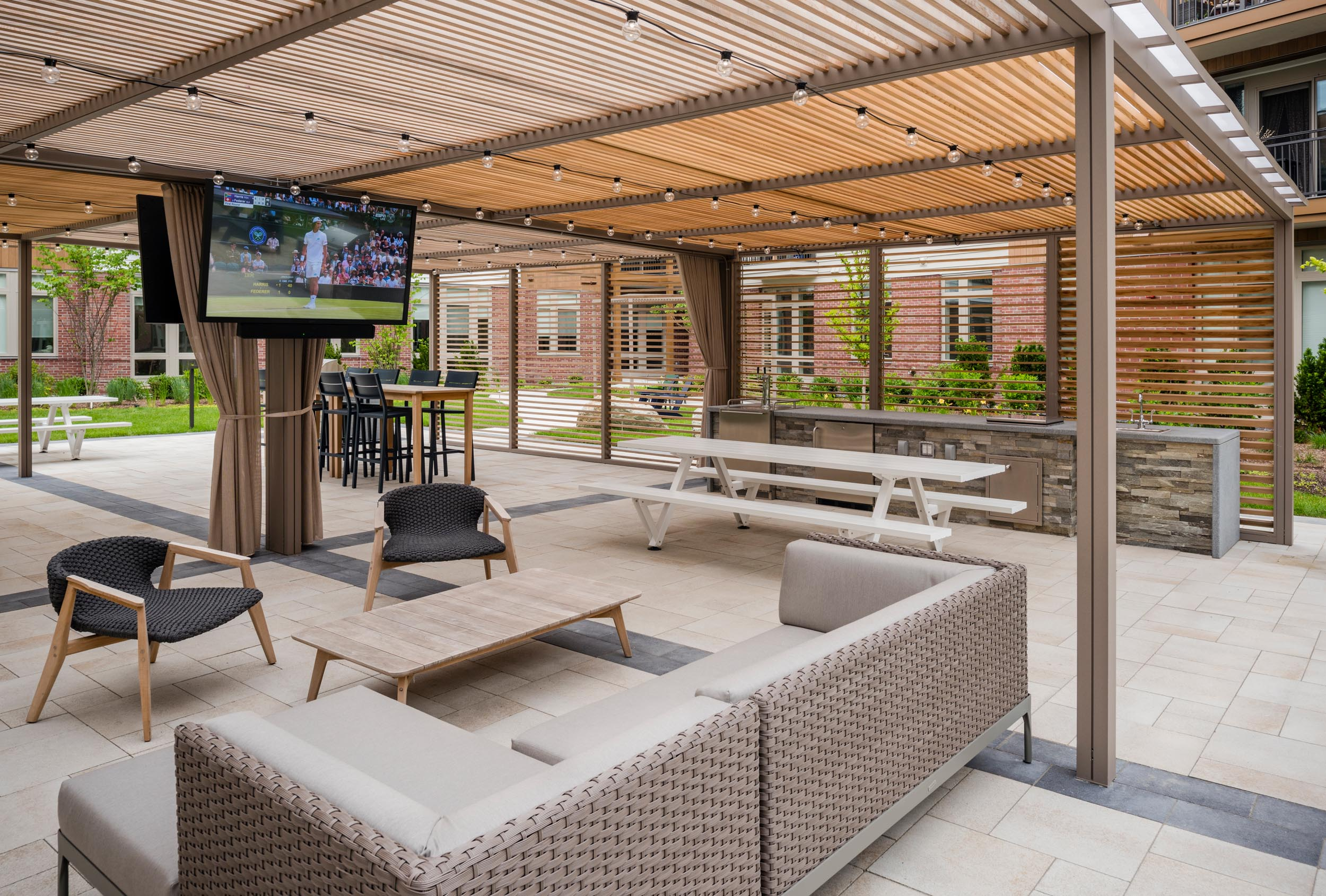 The Kendrick's biergarten, located in an outdoor courtyard and featuring a pergola, seating areas, tables, TVs, and grilling stations
